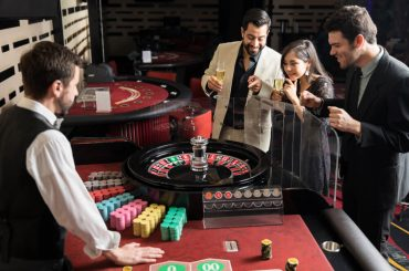 Group of roulette players placing their bets and waiting for the wheel to stop while having a good time in a casino